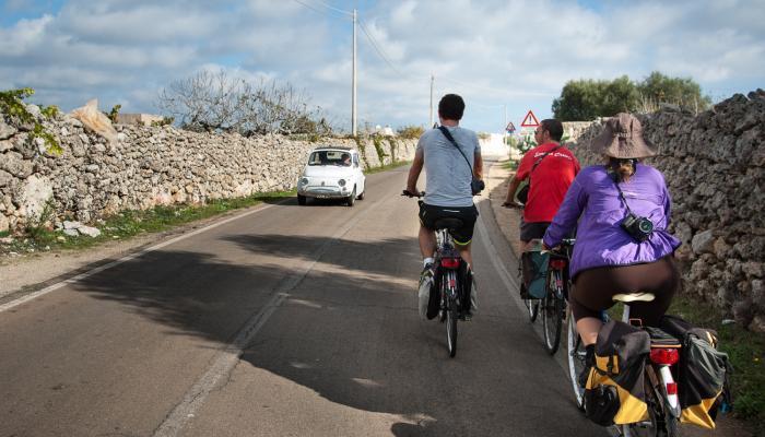 cykeltur på landsvägar med stenmurar och vintage bilar